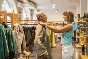 Senior woman trying on coat in a boutique