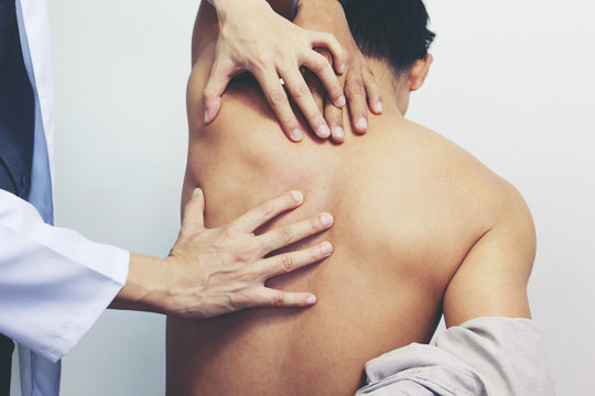 Closeup of Doctor examines or treatment the man with shoulder pain or neck pain on white background,Health concept