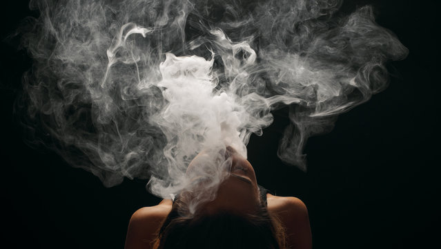 Redhead woman vaping electronic cigarette with smoke on black background closeup. Young woman smoking e-cigarette to quit tobacco. Vapor and alternative nicotine free smoking concept, copy space