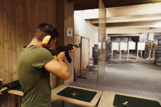 Man aiming with rifle in shooting range