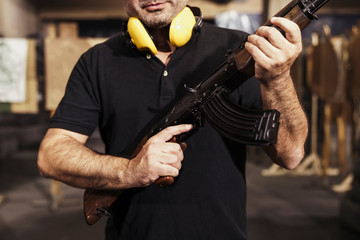 Midsection of man holding rifle in shooting range