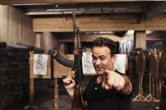 Portrait of man with a rifle pointing his finger in an indoor shooting range