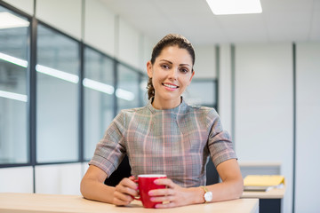 Pretty office worker sitting at desk with red coffee cup