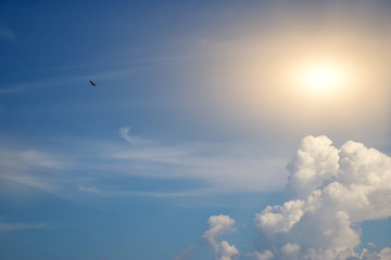 The blue sky and large white clouds with sunlight are passing through and birds are flying through.