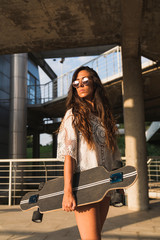 Young woman standing with skateboard in the city