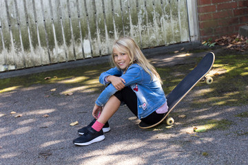 Portrait of smiling blond girl sitting on her skateboard outdoors