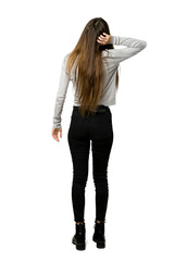 Full-length shot of young girl on back position looking back while scratching head on isolated white background