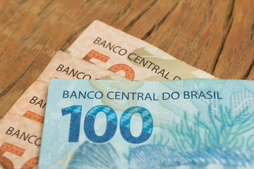 Brazilian currency: Real. Close up of cash bills on rustic wood table.
