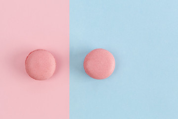 Two pink macarons on divided pink-blue background. Top view with copy space