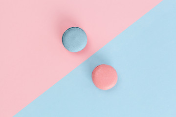 Pink and blue macarons on diagonally divided background in pastel colors. Top view with copy space