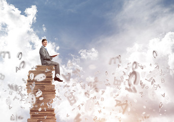 Man student on stack reading book and symbols flying around