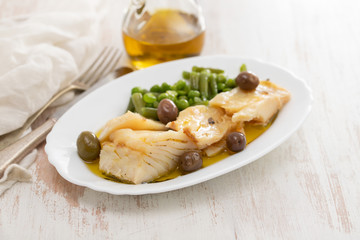 fried cod fish with peas and green beans on white dish