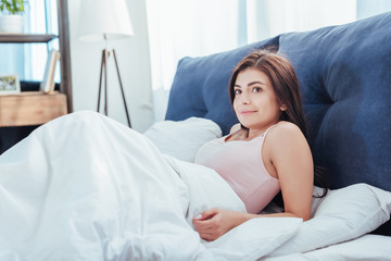 attractive young woman waking up on bed during morning time at home