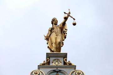 Figur der Justitia auf einem Dachgiebel in Belgien