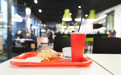 Red tray with Fast Food menu is on the table in the restaurant. French fries, burger, red glass with a cola in the tray against the background of a fast food restaurant. Harmful, caloric food.