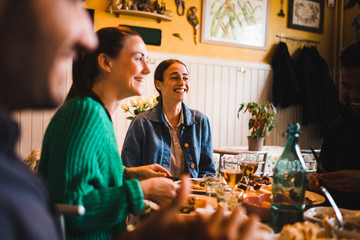 Smiling young women sitting at table in restaurant while enjoying dinner party