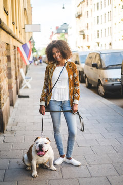 Portrait of smiling mid adult woman standing with dog on sidewalk in city