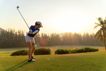 Asian woman golf player doing golf swing tee off on the green sunset evening time, she presumably does exercise.