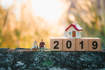 Miniature people, elderly man and woman sitting with mini house on year 2019 wooden block using as job retirement and family concept