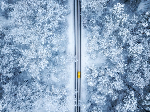 Aerial view of winter road and cars passing by  forest in mountains. drone shot