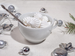 White mug with biscuit biscuits and silver teaspoon in light colors