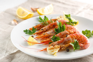 Grilled shrimps with spice, lemon and greenery. Grilled seafood.