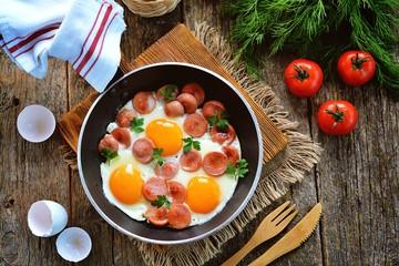 Keuken foto achterwand Gebakken Eieren Homemade fried eggs with sausages in a frying pan on wooden background. Classic breakfast. Top view.