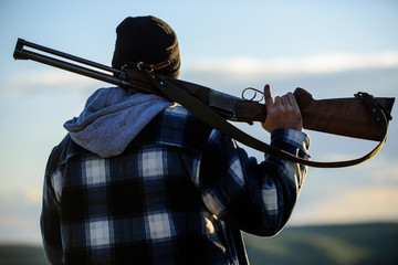 Hunter carry rifle gun on shoulder rear view. Guy hunter spend leisure hunting. Man brutal guy gamekeeper in hat nature background. Hunting masculine hobby leisure concept. Brutality and masculinity