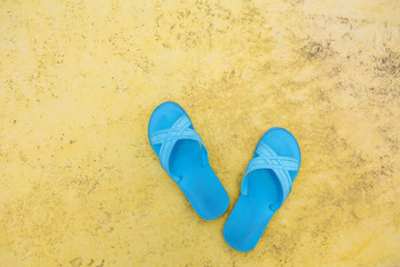 Pair of rubber sandal flip flop footwear on the beach with copy space.