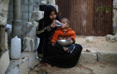 Palestinian woman gives water to her son in Khan Younis in the southern Gaza Strip