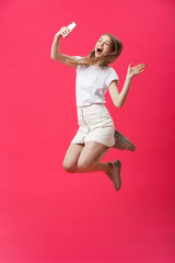 Full length portrait of an excited teenage schoolgirl in uniform with taking a selfie while jumping and showing say hi gesture isolated over pink background.