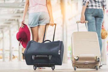 Rear view of two women traveler tourist wearing casual clothes walking with luggage at modern airport or train station in Asia. Young girls holding suitcase or luggage travels, goes abroad,holiday