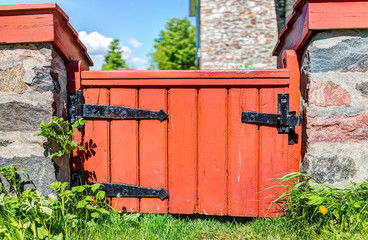 Closeup of small red orange gate to house in summer idyllic peaceful fairy tale garden