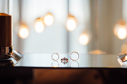 Gold wedding rings lie on the mirror and the light bulbs on the background