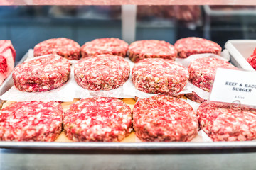 Many beef and bacon burger raw meat sausage patties on tray with pink chunks in butcher store gourmet shop