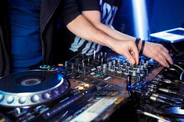 Hands of DJ mix tracks on digital turntable and software on laptop with professional mixing software.Disc jockey play music show