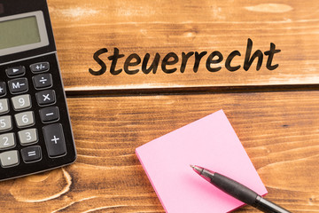 business desk with paper, pen and calculator with german text Steuerrecht, in english tax law