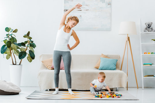 smiling woman doing exercise and looking at cute toddler boy playing with multicolored cubes on carpet in living room