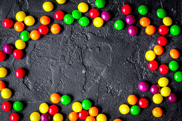 sweets and sugar candies on dark background top view