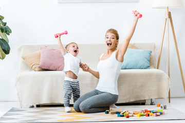 laughing mother and toddler boy holding dumbbells in raising hands and looking at camera on carpet in living room