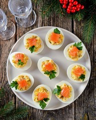 Stuffed chicken eggs with soft cheese, capers and salted salmon. Christmas background.