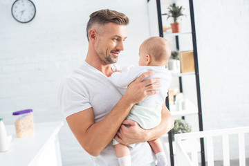 cheerful father holding baby daughter at home