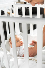 cropped view of happy dad putting cheerful baby into baby crib