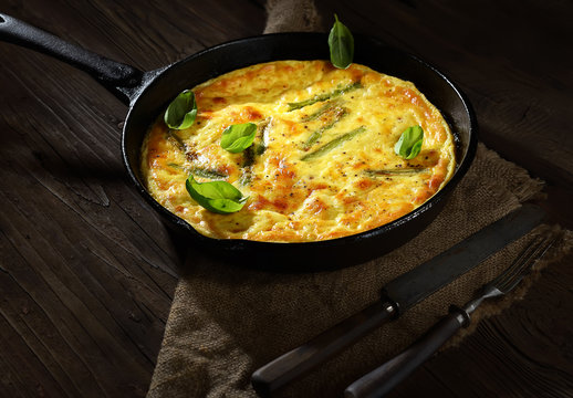 omelet with asparagus in a pan on a wooden background. rustic style.