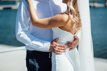 Groom hugs bride tender while wind blows her veil