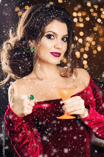 Attractive Girl With Makeup And Hairstyle In Red Dress Keeping Glass