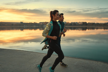 Young man and woman out for a run on the lake at the sunrise Wall mural