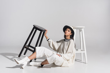 attractive african american girl in stylish white clothes and hat sitting near black and white chairs on white