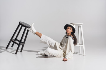 attractive african american young woman in stylish white clothes and hat sitting near black and white chairs on white