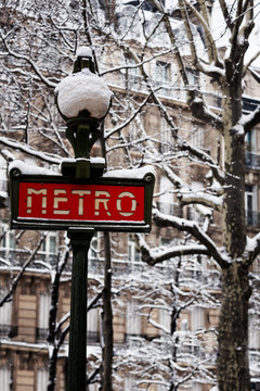 Famous Parisian metro sign after snowfall, France